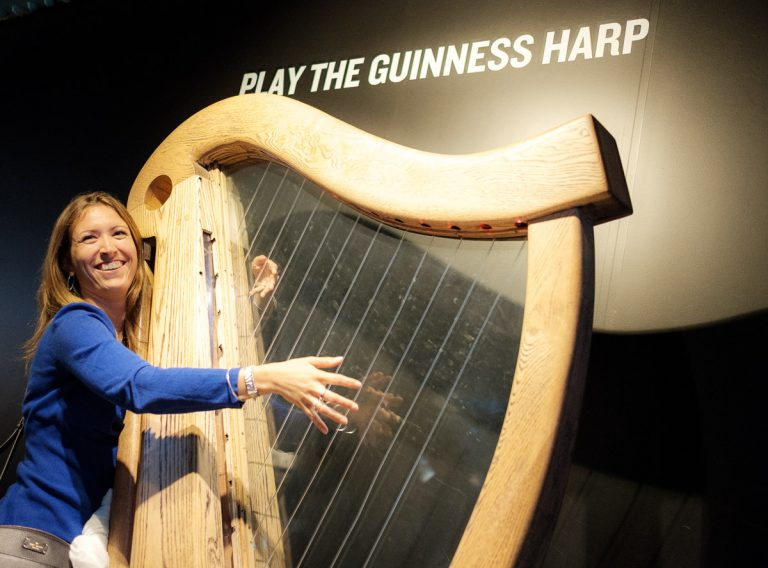 Woman plays harp at The Gathering Festival in Dublin.